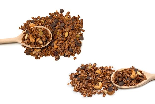 Chocolade muesli granen met noten in een houten lepel. geïsoleerd op een witte achtergrond.