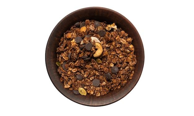 Chocolade muesli granen met noten in een kom oppervlak. geïsoleerd op een witte achtergrond.