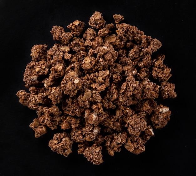 Chocolade muesli, knapperige muesli geïsoleerd op zwarte achtergrond