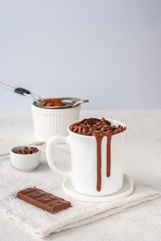 Chocolade mug cake in witte kop met chocoladedruppels en cocapoeder