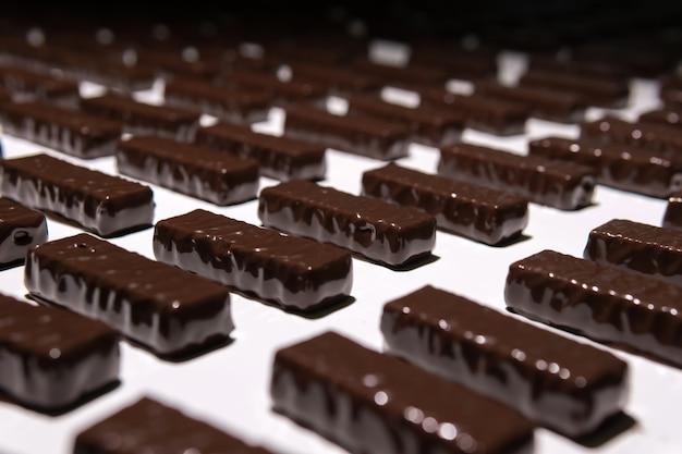 Chocolade net gegoten met vloeibare chocolade op een transportband van een zoetwarenfabriek close-up