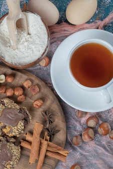 Chocolade noten koekjes op een houten bord geserveerd met kaneel en een kopje thee.