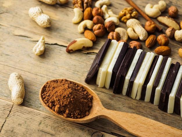 Chocolade, noten, rozijnen en cacaolepel op houten oppervlak