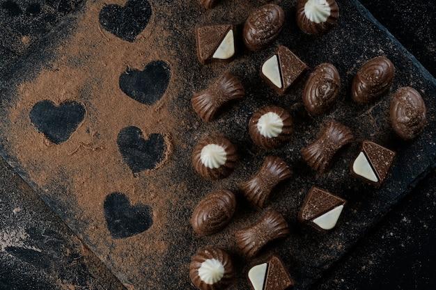 Chocolade op zwarte steen met cacaopoeder die harten vormt