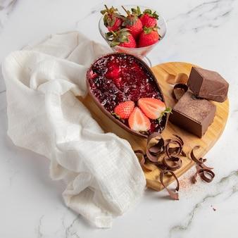 Chocolade paasei gevuld met aardbeienjam naast blokken en chocoladeschilfers en een kom aardbeien. pasen-landschap in hartvorm.