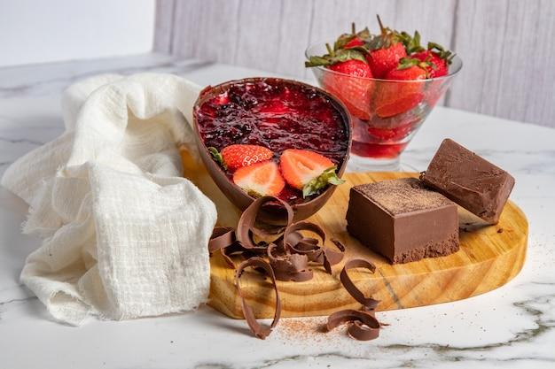 Chocolade paasei gevuld met aardbeienjam naast blokken en chocoladeschilfers en een kom aardbeien. pasen landschap.
