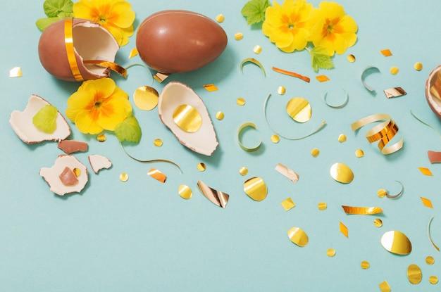 Chocolade paasei met gouden confetti en lentebloemen op blauwe munt papier achtergrond