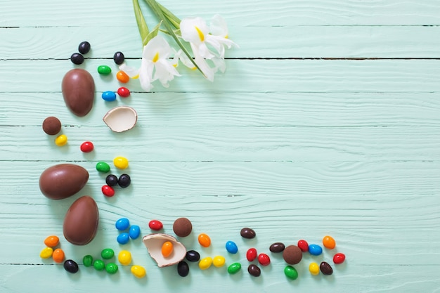 Chocolade paaseieren en bloemen op groene houten oppervlak
