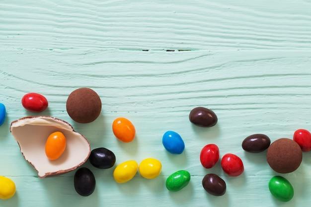 Chocolade paaseieren en snoepjes op groene houten oppervlak