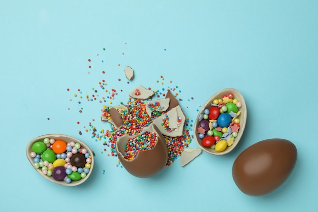 Chocolade paaseieren met hagelslag en snoep op blauw