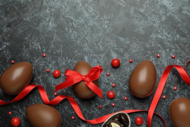 Chocolade paaseieren met snoepjes op zwarte smokey oppervlak