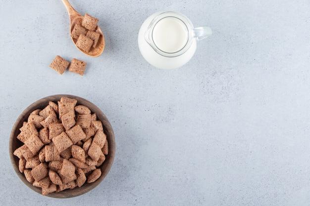 Chocolade pads cornflakes in houten kom met fles melk. hoge kwaliteit foto