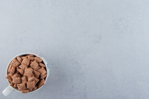 Chocolade pads cornflakes in keramische mok op stenen achtergrond. hoge kwaliteit foto