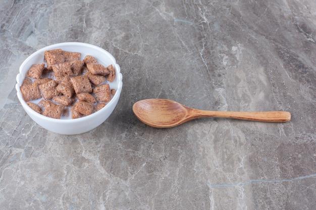 Chocolade pads cornflakes in witte kom met een houten lepel.