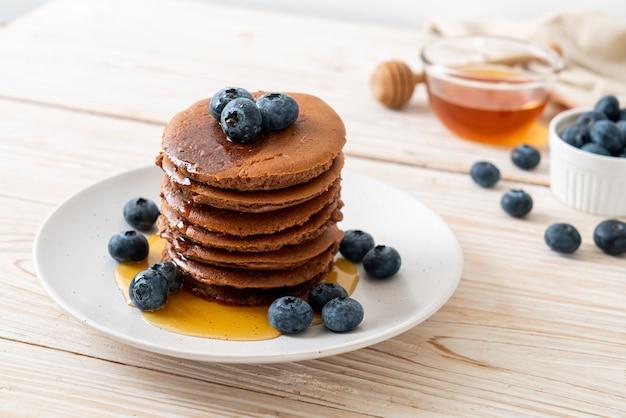 Chocolade pannenkoek stapel met bosbessen en honing op plaat