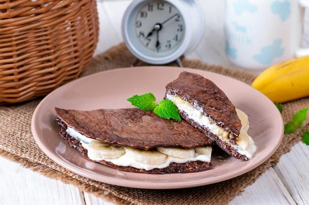 Chocolade pannenkoek van havermout met banaan op een houten achtergrond, gezond ontbijt