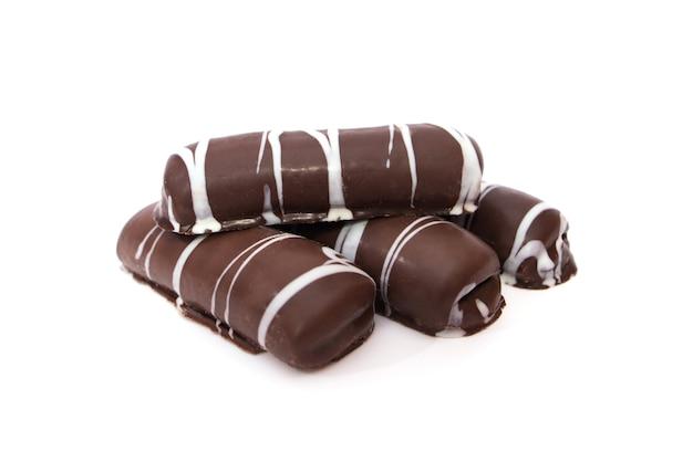 Chocolade peperkoek koekjes met witte suikerglazuur op een witte achtergrond.