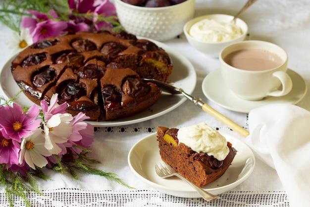 Chocolade pruimentaart met slagroom, geserveerd met cacao. rustieke stijl.