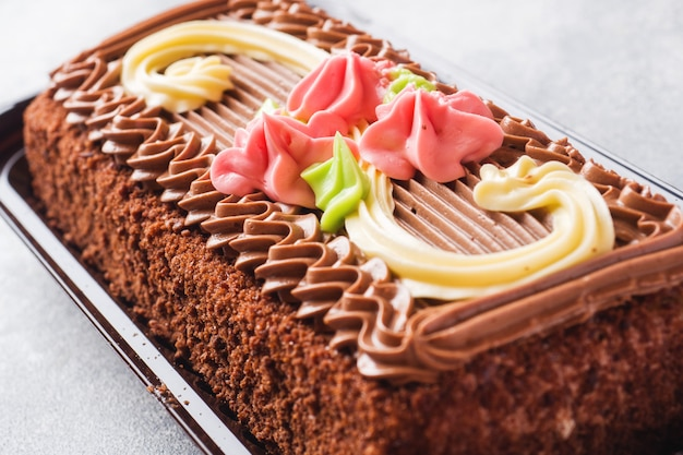 Chocolade rechthoekige cake versierd met crème rozen op een lichte tafel. zoet eten is een banketbakkerij. kopieer ruimte