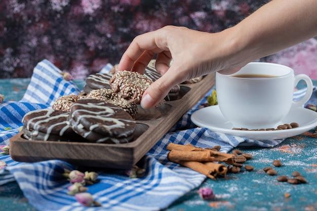 Chocolade sesamkoekjes geserveerd met een kopje drank.