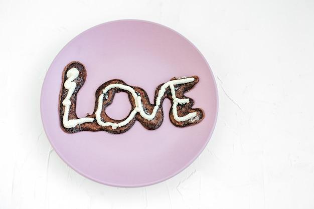 Chocolade smakelijke cake met room op de purpere plaat.