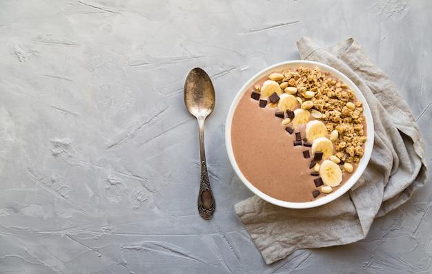 Chocolade smoothie kom met bananen, muesli en pinda's op lichtgrijze betonnen ondergrond. gezond vegetarisch ontbijt. bovenaanzicht met ruimte voor tekst.