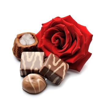 Chocolade snoep en rode roos geïsoleerd.