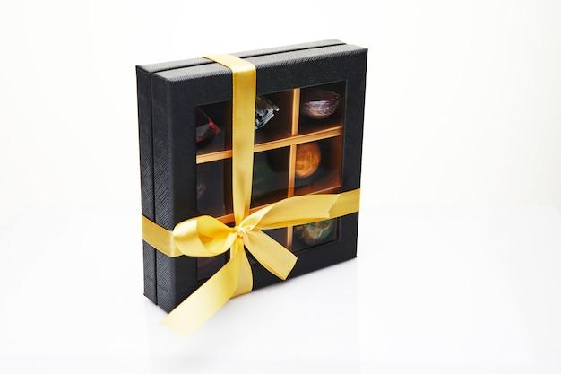 Chocolade snoepjes in de vorm van edelstenen in een doos op een wit oppervlak