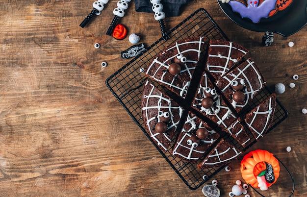 Chocolade spinnenweb brownies met snoep spinnen, zelfgemaakte lekkernijen voor halloween op rustieke houten achtergrond. bovenaanzicht met kopieerruimte
