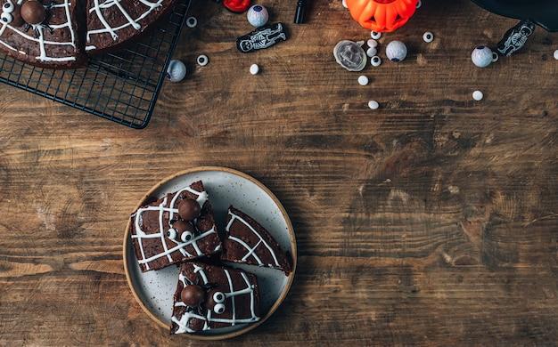 Chocolade spinnenweb brownies met snoep spinnen, zelfgemaakte lekkernijen voor halloween op rustieke houten achtergrond. bovenaanzicht met plaats voor tekst