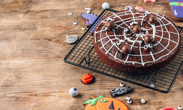 Chocolade spinnenweb brownies met snoep spinnen, zelfgemaakte lekkernijen voor halloween op rustieke houten achtergrond. selectieve focus met kopieerruimte