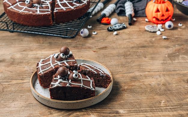 Chocolade spinnenweb brownies met snoep spinnen, zelfgemaakte lekkernijen voor halloween op rustieke houten achtergrond. selectieve focus met plaats voor tekst