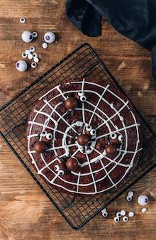 Chocolade spinnenweb brownies met snoep spinnen, zelfgemaakte lekkernijen voor halloween op rustieke houten achtergrond