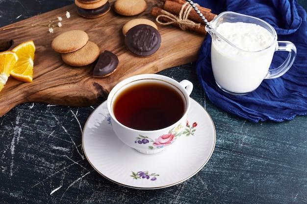 Chocolade spons koekjes op een houten bord met gestremde melk en thee.