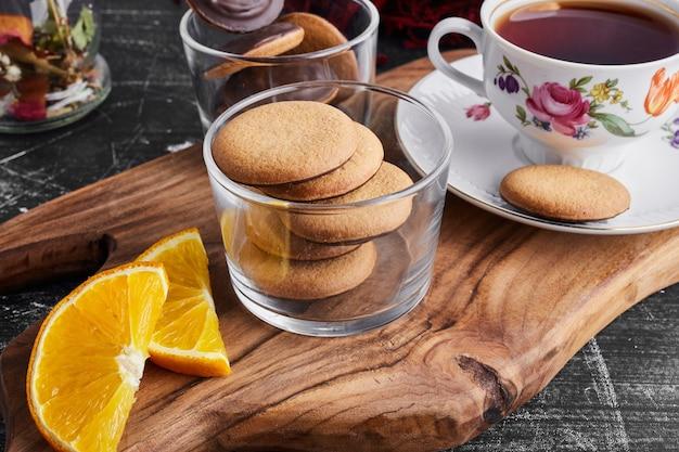 Chocolade spons koekjes op een houten bord met sinaasappel en thee.