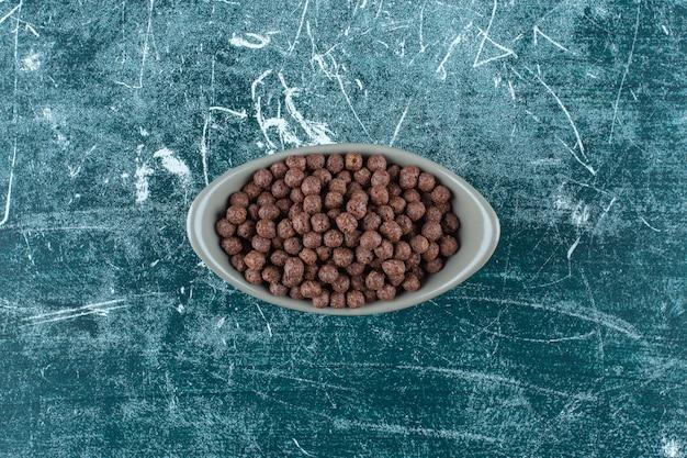 Chocolade suikermaïs ballen in een kom, op de blauwe achtergrond. hoge kwaliteit foto