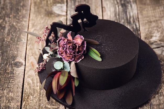 Chocolade velours cake versierd met prachtige bloemen en bladeren