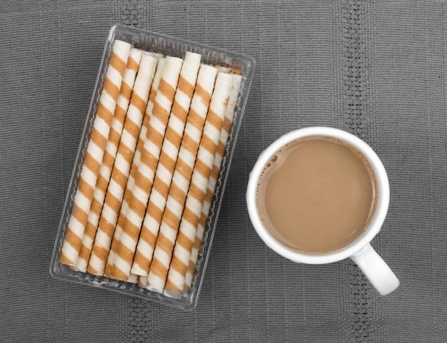 Chocolade wafel sticks en kopje koffie met melk op grijze achtergrond bovenaanzicht