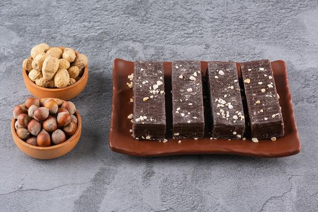 Chocolade wafeltjeplakken met noten en pinda's op grijs.