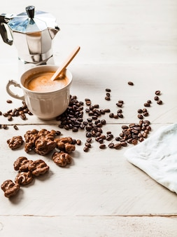 Chocolade walnoot; gebrande koffiebonen en espresso koffie op houten tafel