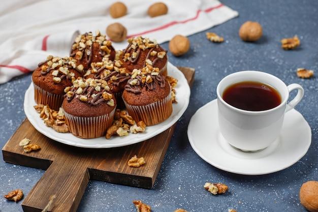Chocolade-walnootmuffins met koffiekop met walnoten op donkere oppervlakte