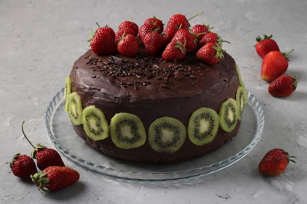 Chocolade zelfgemaakte cake versierd aardbeien en kiwi gelegen op grijze betonnen achtergrond, horizontaal formaat, close-up
