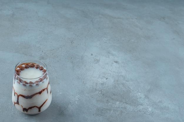 Chocoladeballen in een melkglas, op de blauwe achtergrond.