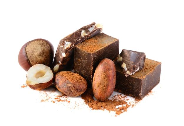 Chocoladeblokken met cacaobonen en noten die op witte achtergrond worden geïsoleerd