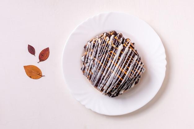 Chocoladebroodje met papaverzaden op een lichte achtergrond. boterbroodje en herfstbladeren.