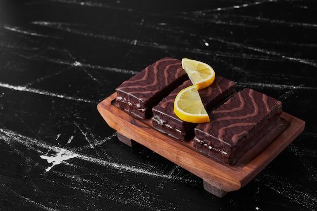 Chocoladebrownies op een houten schotel met citroen.