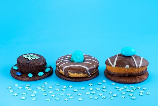 Chocoladebrownies van een vooraanzicht samen met cakes en donuts op blauw, het koekjeskleur van de suikercake
