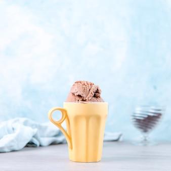Chocoladebruin ijs in een gewone gele mok, op blauw.