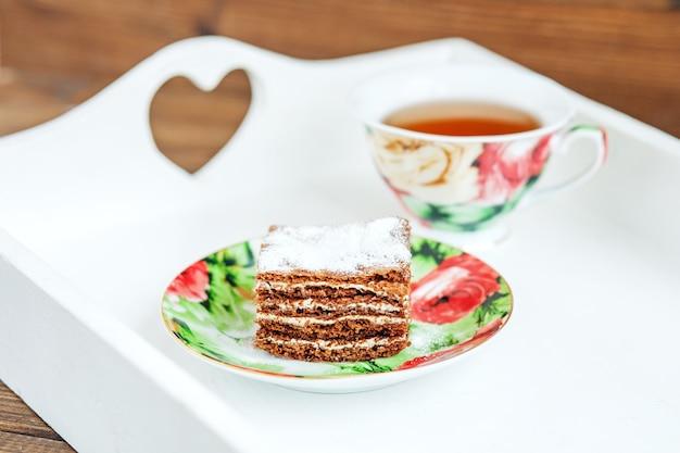 Chocoladecake en een kop hete thee op een wit dienblad.