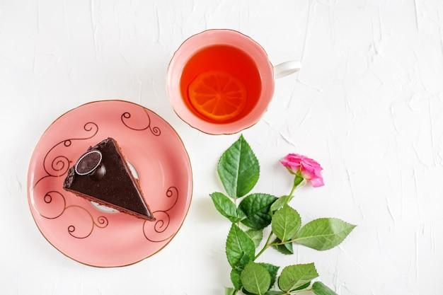 Chocoladecake en hete thee op een dienblad op bilomuuachtergrond.